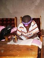 Makau (Florences youngest brother) doing homework with the help of Natalies headlamp